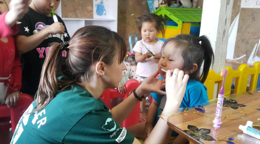 A high school student teaching children how to brush teeth during our medical project abroad for teenagers.